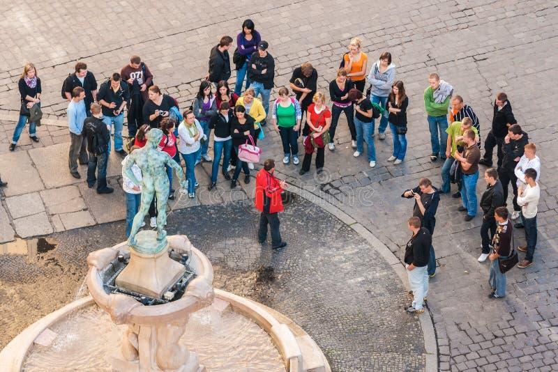 Turister med den turist- handboken samlade framme av statyn av den nakna fäktaren, Wroclaw arkivfoto