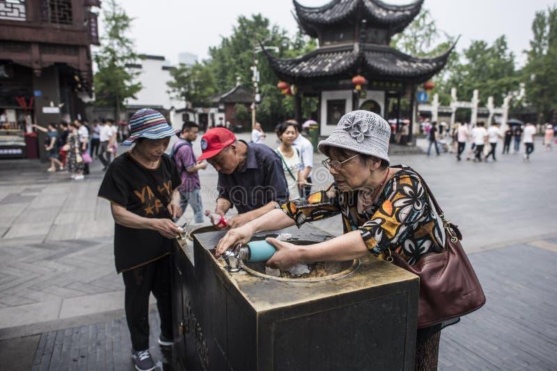 Turister med direkt dricksvatten i sceniska fläckar arkivfoto