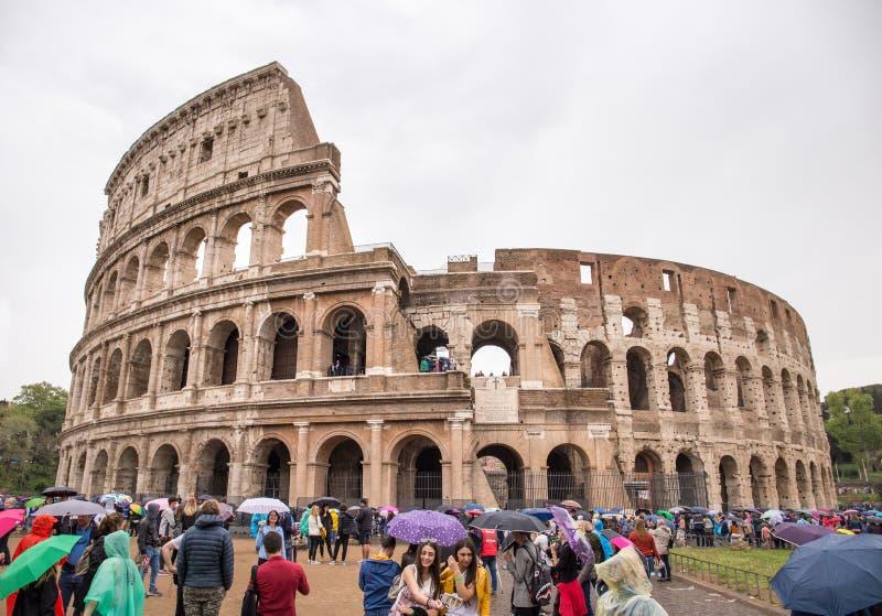 Turister med paraplyer som väntar i kö på Colosseum royaltyfri fotografi