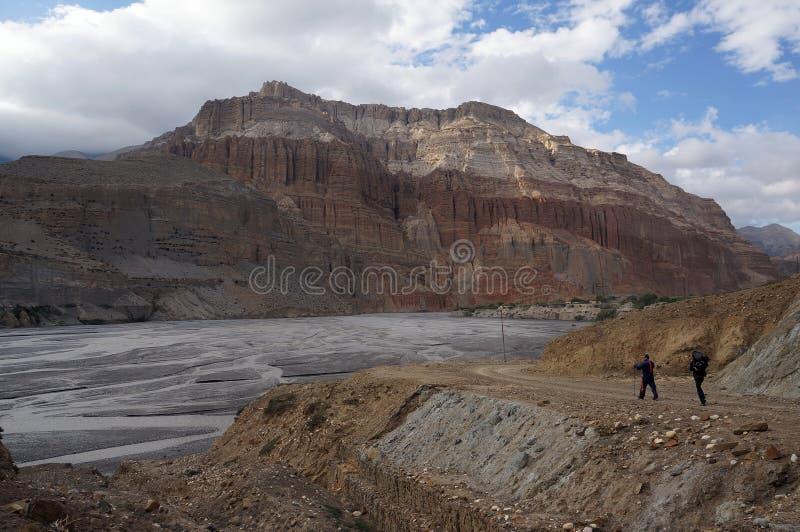 Turister med trekking pinnar promenerar Kali Gandaki River mot bakgrunden av de Chhusang klipporna royaltyfri fotografi