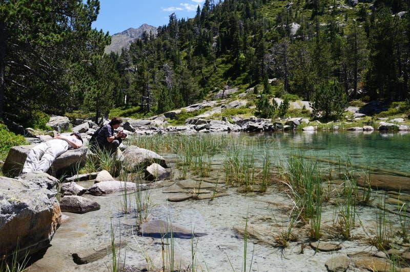 Turister nära den bergiga sjön royaltyfria bilder