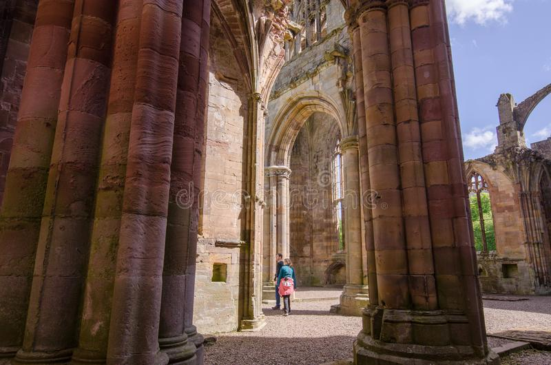 Turister observera arkitektoniska detaljer av Melroseabbotskloster fotografering för bildbyråer