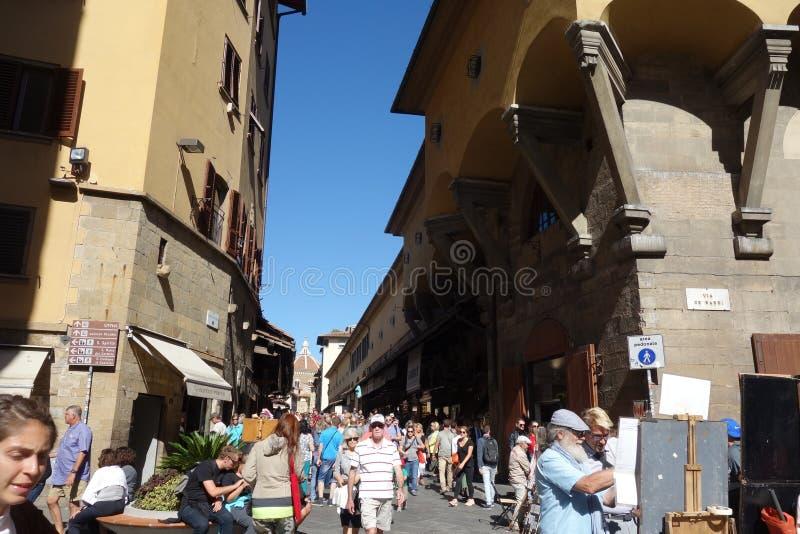 Turister och konstnärer på Ponte Vecchio i Florence fotografering för bildbyråer
