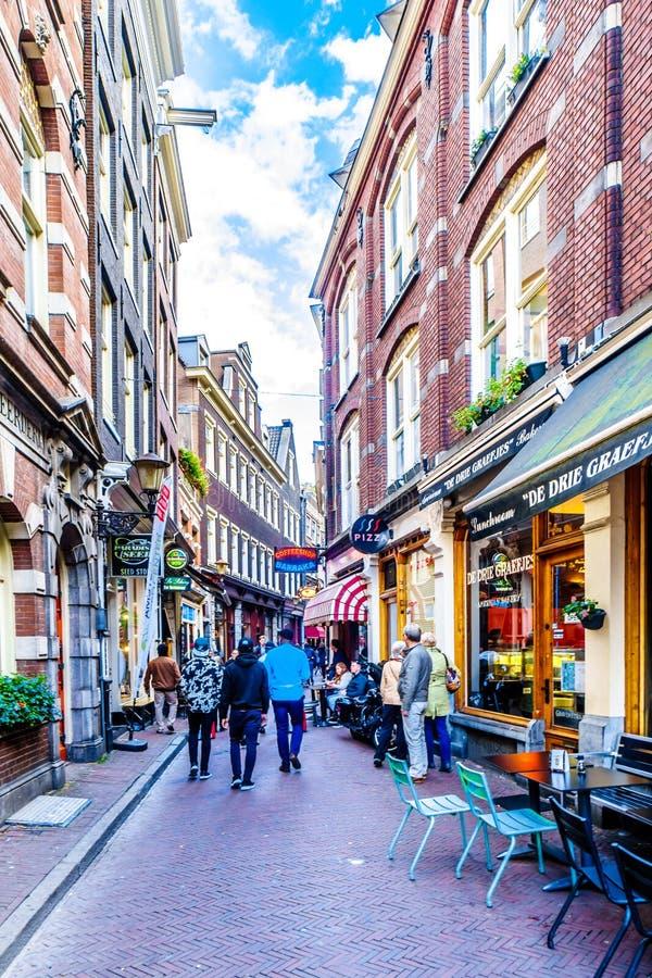 Turister och lokaler i den smala Gravenstraaten i den historiska mitten av Amsterdam arkivbild