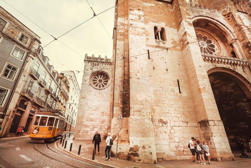 Turister och spårvagn som kör runt om den 12th århundradeLissabon domkyrkan på den historiska stadsgatan arkivbilder