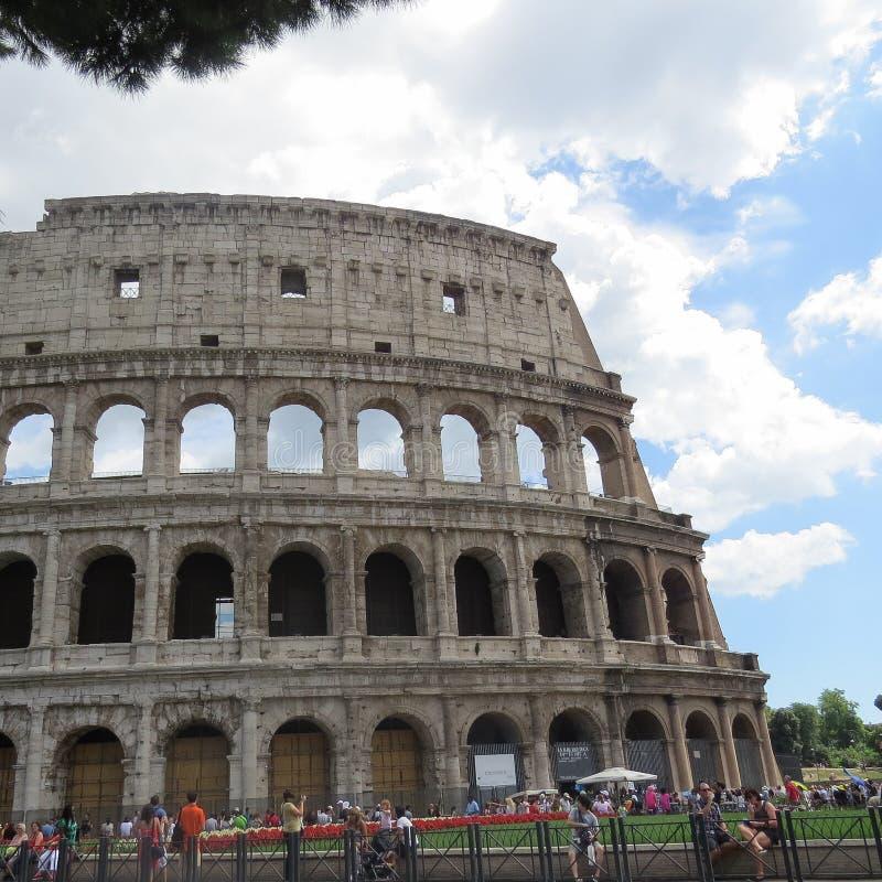 Turister och väggen av Colosseumen i Rome mot den blåa molniga himlen royaltyfria foton