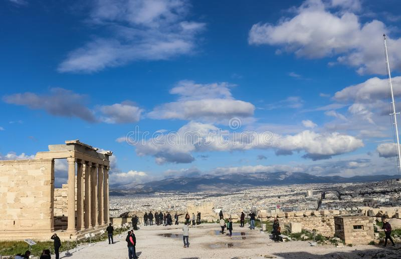 Turister på på akropolen med regnpölar och staden av Aten och ett berg i bakgrunden under en dramatisk molnig himmel royaltyfri foto