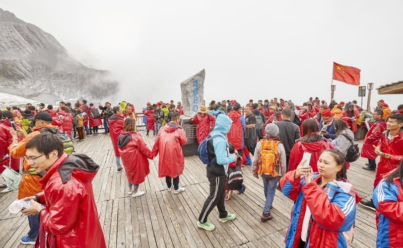 Turister på den Jade Dragon Snow Mountain visningplattformen som täckas med moln royaltyfri bild
