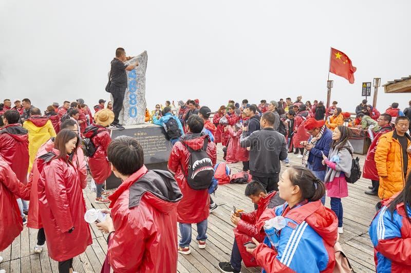 Turister på den Jade Dragon Snow Mountain visningplattformen som täckas med moln arkivfoton