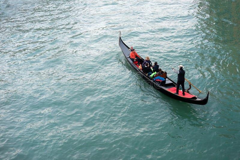 Turister på en typisk gondol i en Venetian kanal royaltyfria bilder