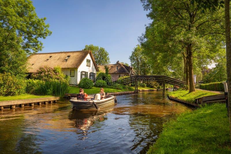 Turister på ett fartyg i byn av Giethoorn, Nederländerna royaltyfria bilder