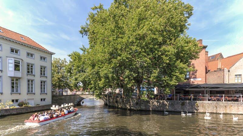 Turister på ett fartyg i en av de talrika kanalerna av Bruges, Flanders i Belgien arkivbild