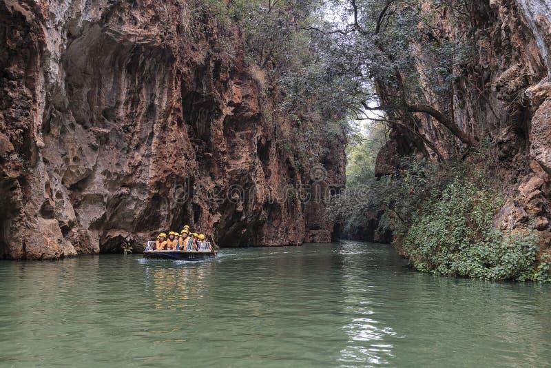Turister på ett fartyg i floden i Jiuxiang det sceniska området i Yunnan i Kina Thee Jiuxiang grottaområde är nära stenskogen royaltyfria bilder