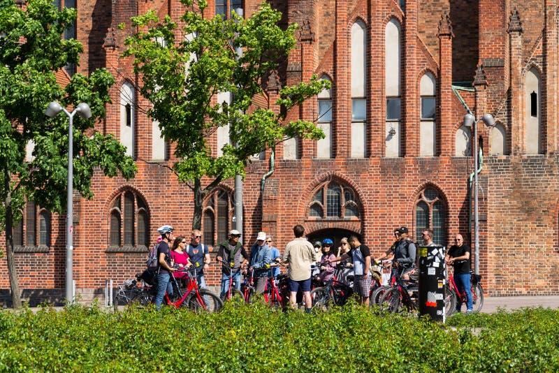 Turister på stadscykeln turnerar stående framme av den evangelic kyrkan för St Marys, Marienkirche i Berlin, Tyskland royaltyfri bild