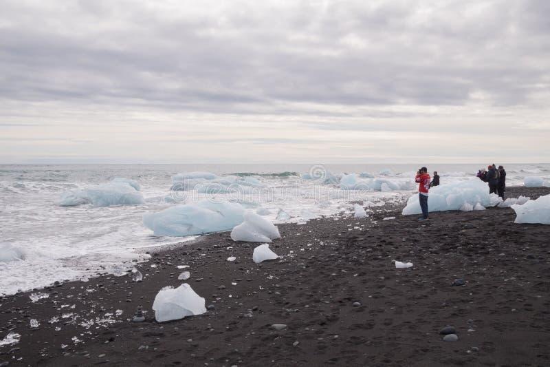 Turister på stranden på den Jokulsarlon glaciärlagun, Island royaltyfri foto
