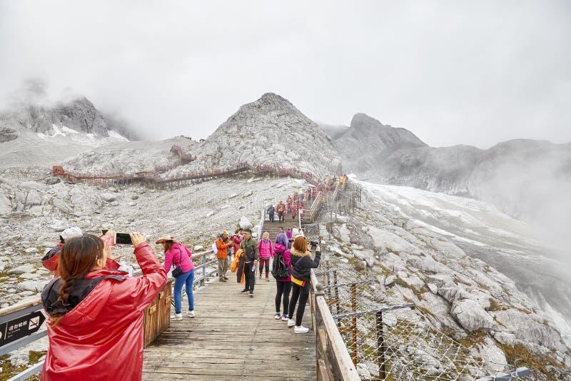 Turister på vägen upp till den Jade Dragon Snow Mountain visningplattformen arkivfoto