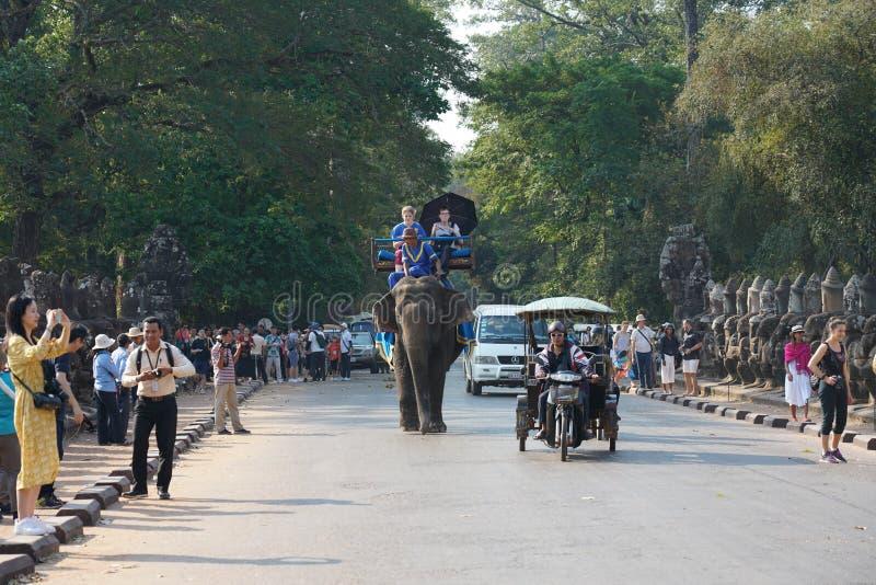 Turister passerar den södra porten av Angkor Thom på en elefant royaltyfri fotografi