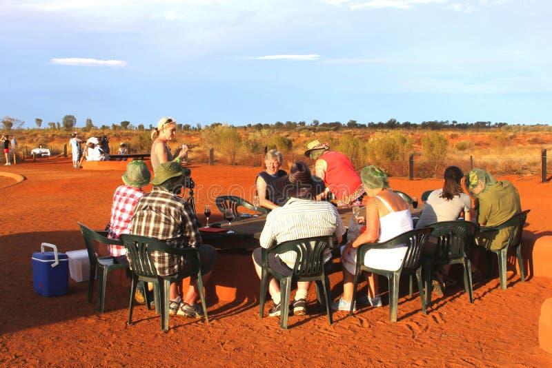 Turister picknicking i den röda cengtren av Australien nära Ayers vaggar fotografering för bildbyråer