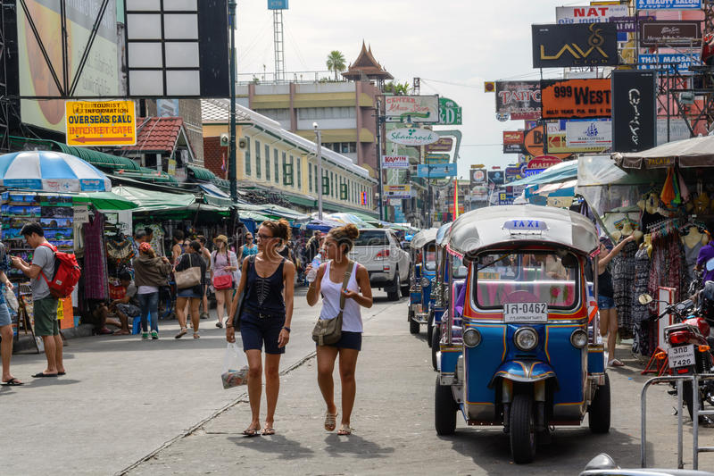 Turister promenerar den fotvandraretillflyktsortKhao San vägen och tuktuk i Bangkok, royaltyfri foto