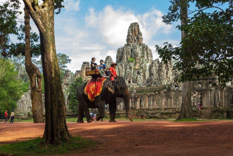 Turister rider elefanter förbi den Bayon templet i Cambodja fotografering för bildbyråer