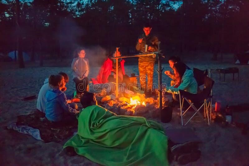 Turister runt om lägerelden på natten royaltyfri foto