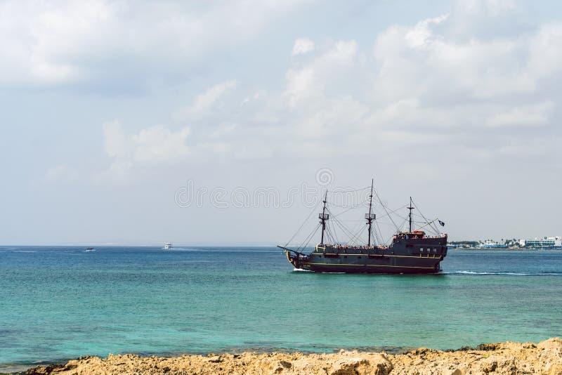 Turister simmar i havet nära piratkopierar skeppsvartpärlan, Cavo Greco, Cypern royaltyfri fotografi