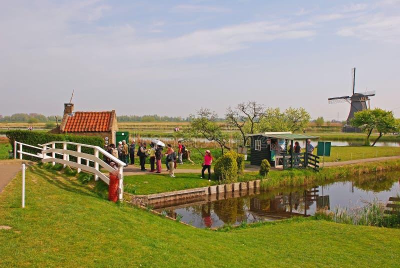 Turister som besöker den berömda väderkvarnen på Kinderdijk, Nederländerna royaltyfri bild