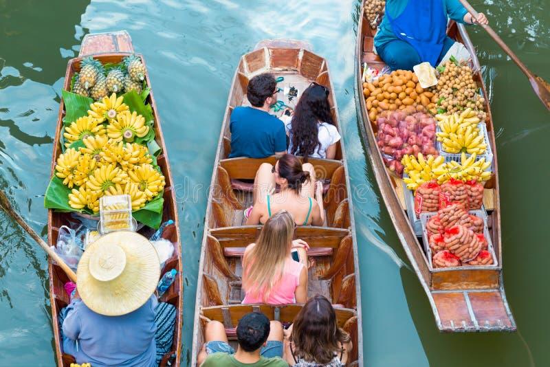 Turister som besöker med fartyget på Damnoen Saduak som svävar marknaden royaltyfri foto