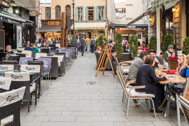 Turister som besöker och har lunch på det utomhus- restaurangkafécentret i Bucharest arkivbild