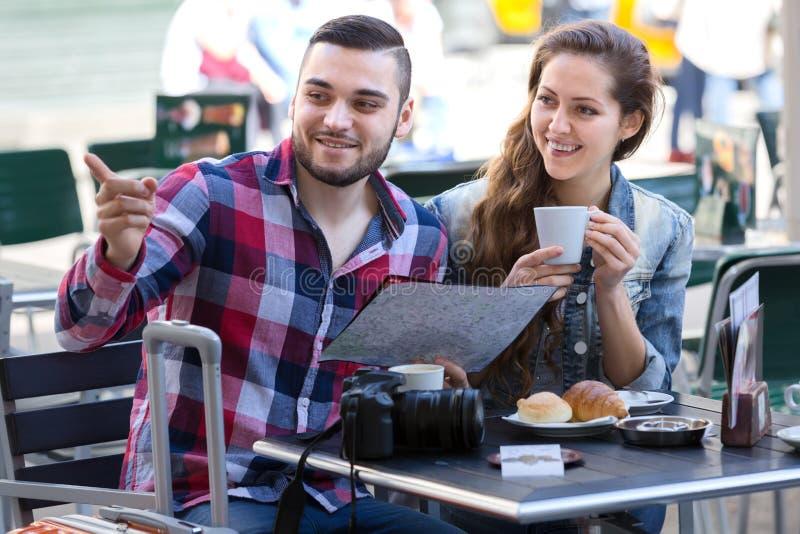 Turister som dricker kaffe- och undersökaöversikten arkivfoton