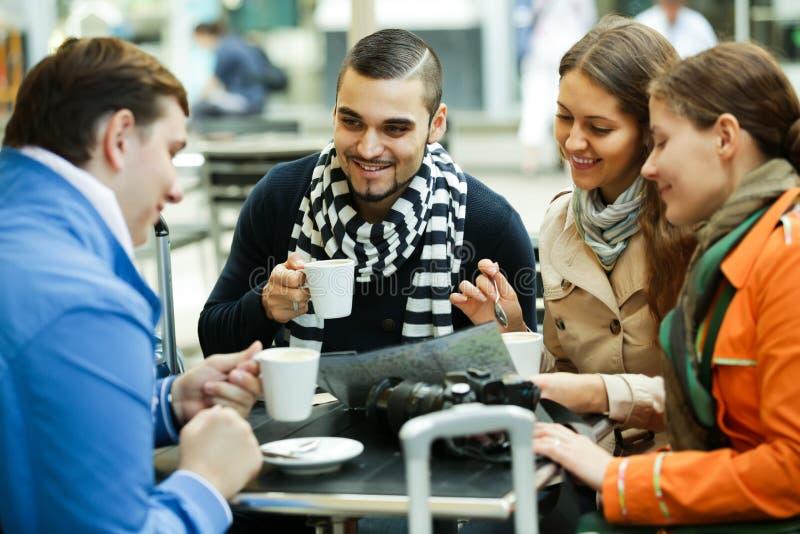 Turister som dricker kaffe på kafét och den läs- stadsöversikten arkivfoton