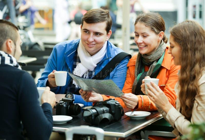 Turister som dricker kaffe på kafét och den läs- stadsöversikten royaltyfria foton