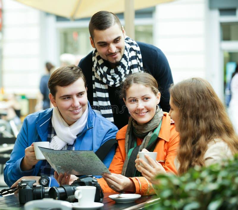 Turister som dricker kaffe på kafét och den läs- stadsöversikten royaltyfri foto