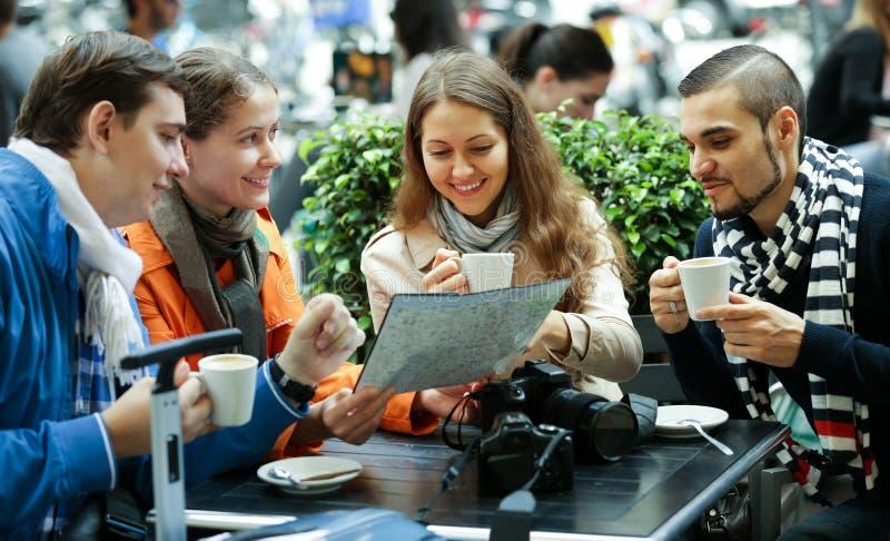 Turister som dricker kaffe på kafét och den läs- stadsöversikten royaltyfri fotografi
