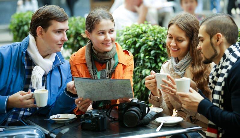 Turister som dricker kaffe på kafét och den läs- stadsöversikten arkivfoto