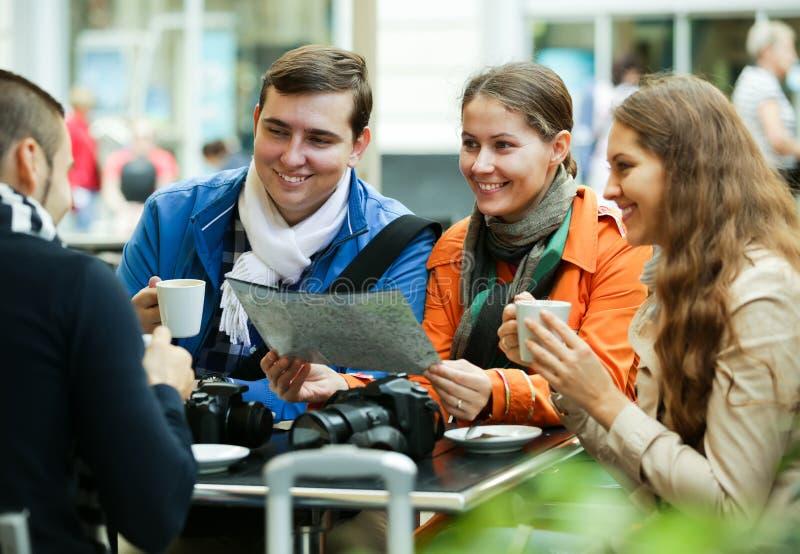 Turister som dricker kaffe på kafét och den läs- stadsöversikten fotografering för bildbyråer