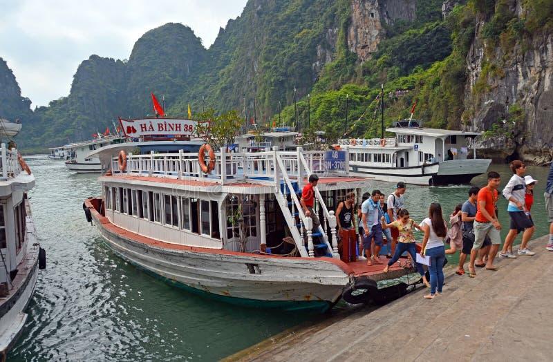 Turister som går att se grottorna på Halong skälla, Vietnam royaltyfri foto