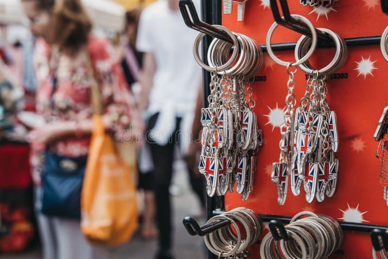 Turister som går förbi en ställning med den nyckel- kedjan för souvenir på försäljning på royaltyfria bilder