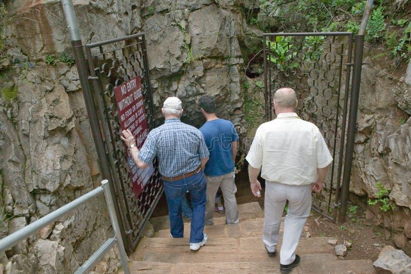 Turister som går in i grottan på vaggan av mänskligheten, en världsarv i Gauteng Province, Sydafrika, platsen av 2 millio 8 royaltyfri fotografi