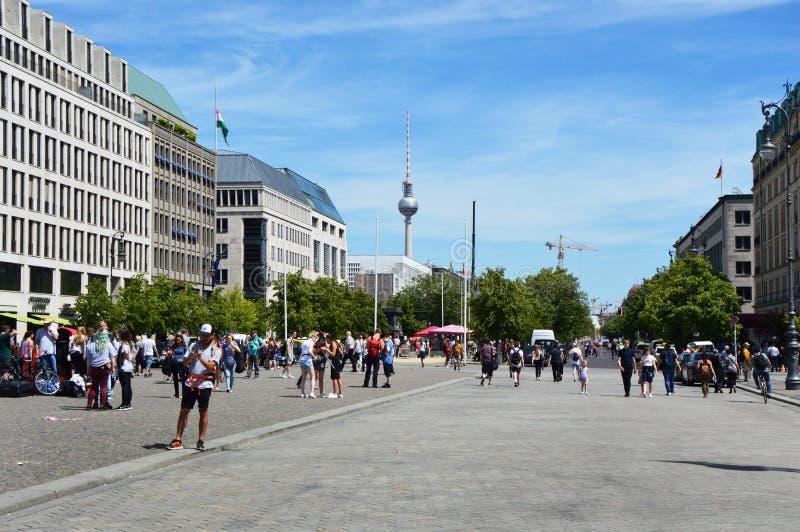 Turister som går i Pariser Platz och TV, står högt på bakgrunden, Berlin, Tyskland arkivfoton