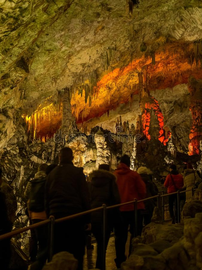 Turister som går på banan bland de upplysta stalaktiten och stalagmina royaltyfri bild