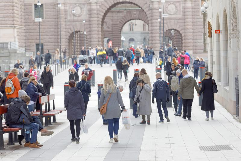 Turister som går på famouesgatan Drottningatan i Stockhol arkivfoto