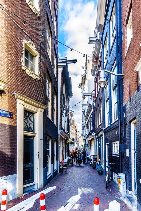 Turister som går till och med den smala Raamsteeg fönstergränden i den historiska mitten av Amsterdam arkivbild