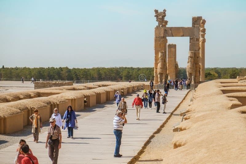 Turister som går till och med, fördärvar av de forntida nationerna för porten allra, Iran royaltyfria bilder