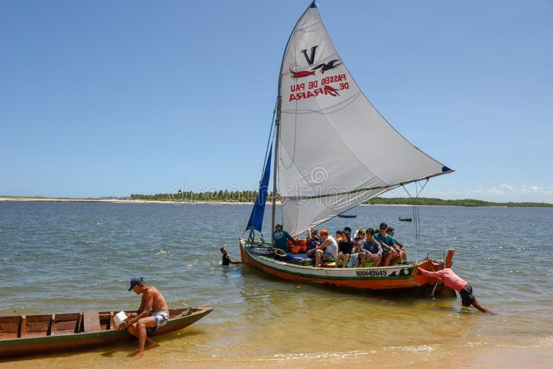 Turister som gör en tur på en segelbåt på Barra de Cunhau på Brasilien arkivbilder