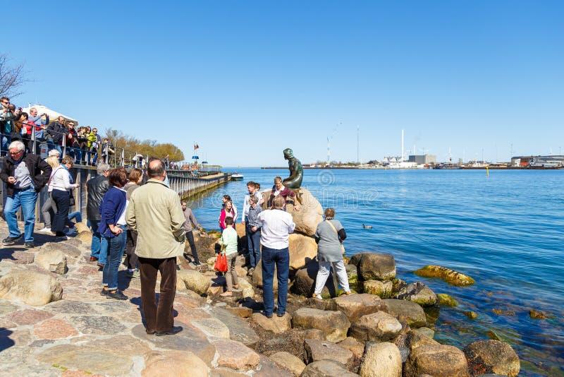 Turister som håller ögonen på den lilla sjöjungfrun, brons statyn som visar en sjöjungfru royaltyfri fotografi