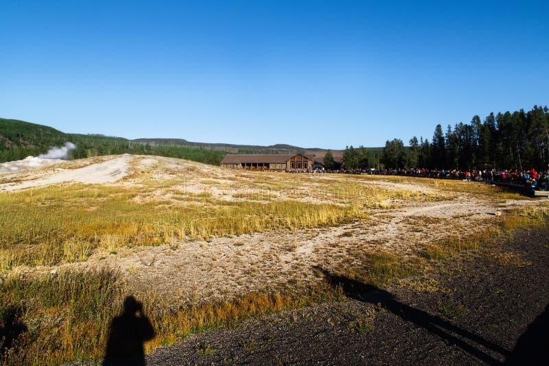 Turister som håller ögonen på gammalt troget få utbrott i den Yellowstone nationalparken royaltyfri fotografi