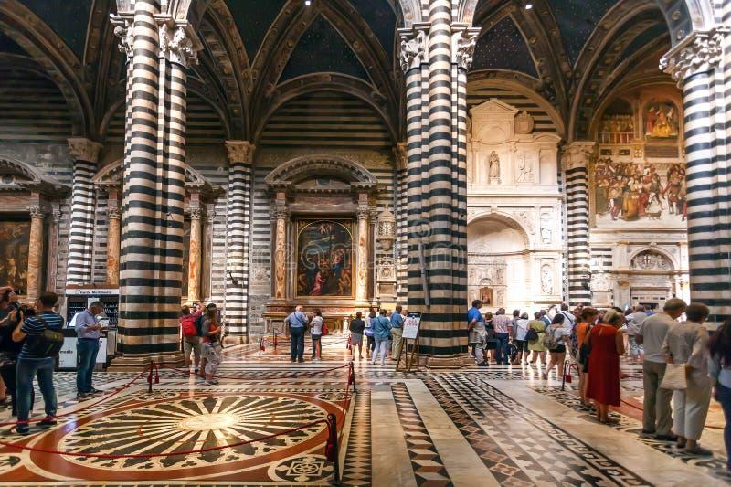 Turister som håller ögonen på inre av 14th århundradeDuomodi Siena med mosaiker och garnering royaltyfri fotografi