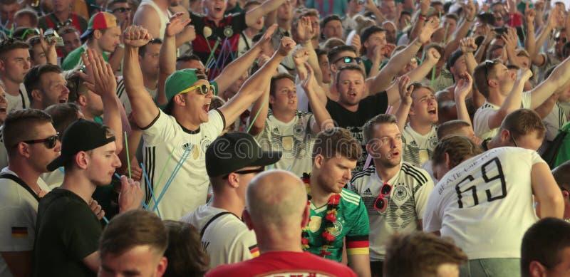 Turister som håller ögonen på världsfotbollsmatchen på den jätte- skärmen under deras ferier i mallorca som gör poäng ögonblick royaltyfria foton