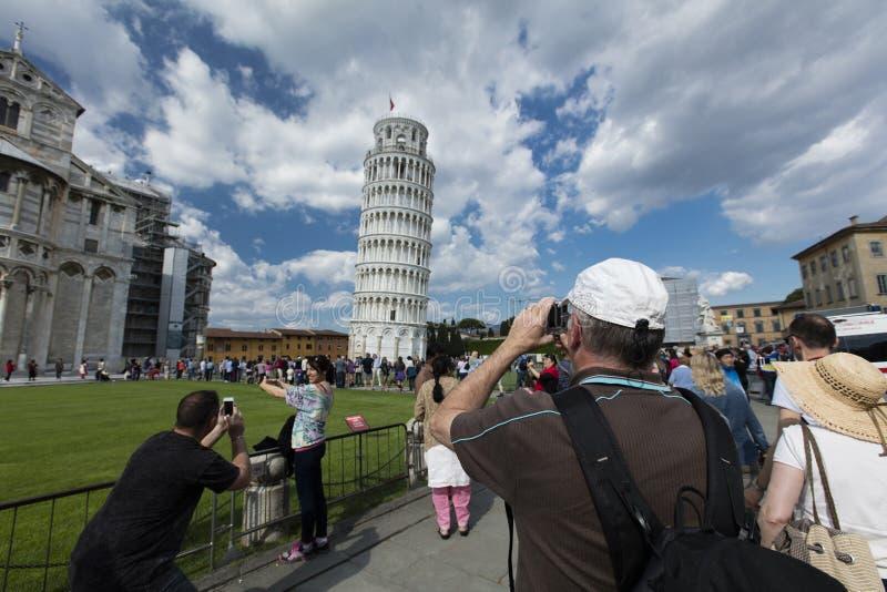 Turister som har gyckel som poserar för bilder med den medeltida belltoweren av den Pisa domkyrkan, vet gemensamt som det lutande fotografering för bildbyråer
